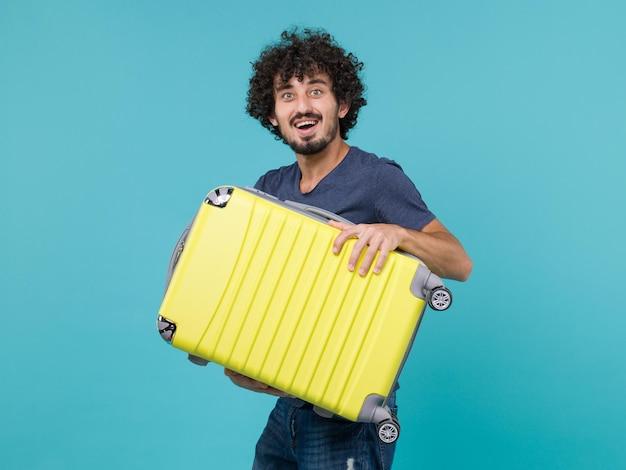 青に大きな黄色のスーツケースを持って休暇中の男