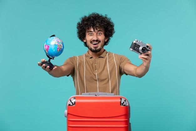 Человек в отпуске держит маленький глобус и фотоаппарат на голубом