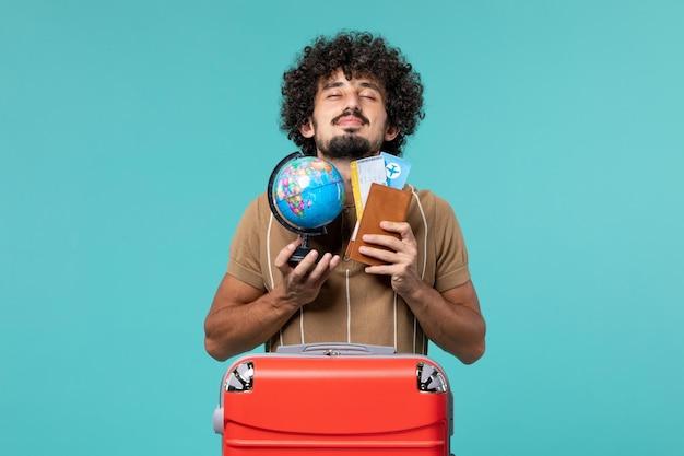 青の小さな地球儀とチケットを持って休暇中の男