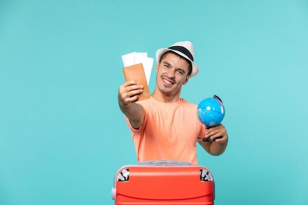 水色の小さな地球儀とチケットを持って休暇中の男