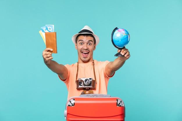 Человек в отпуске держит маленький глобус и билеты на голубом