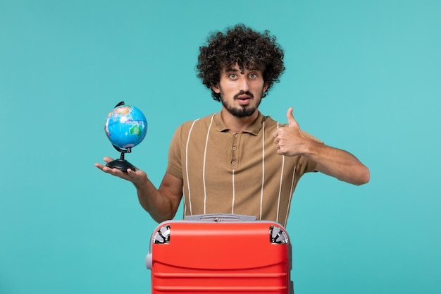 Человек в отпуске держит маленький глобус с красной сумкой на синем