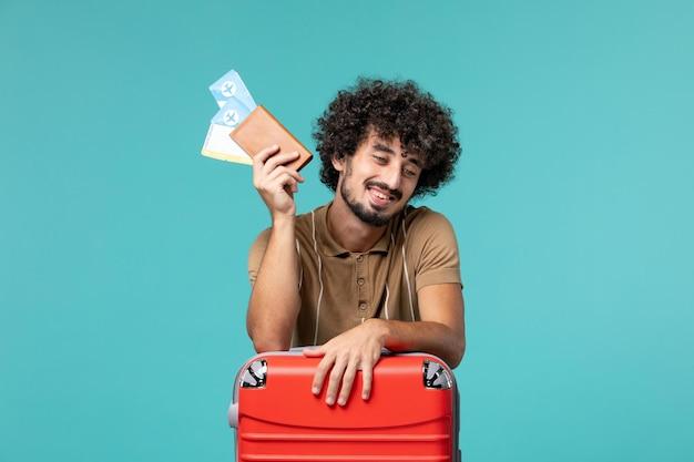 Человек в отпуске держит билеты и прислоняется к своей красной сумке на синем