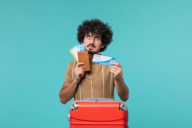 Человек в отпуске держит билеты и думает о синем