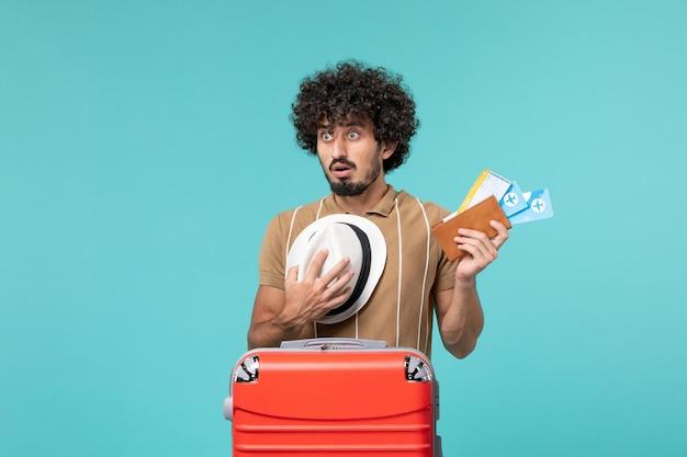 青い壁にチケットを持っている休暇中の男