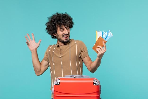 Человек в отпуске держит билеты на синем