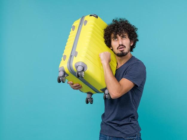 밝은 파란색에 노란색 가방을 들고 휴가에 남자