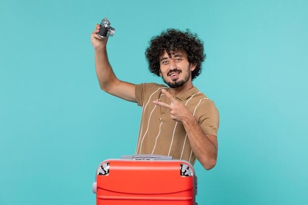 Человек в отпуске с большим красным чемоданом фотографирует с камерой на синем