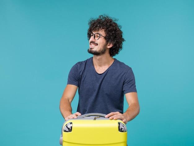 Человек в отпуске с большим чемоданом на синем