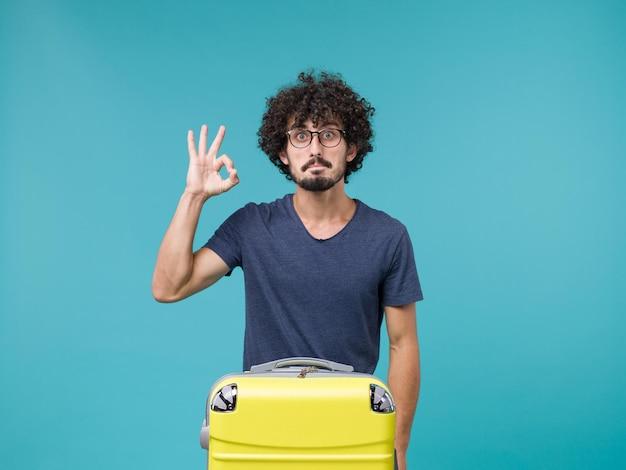青に大きなスーツケースを持って休暇中の男