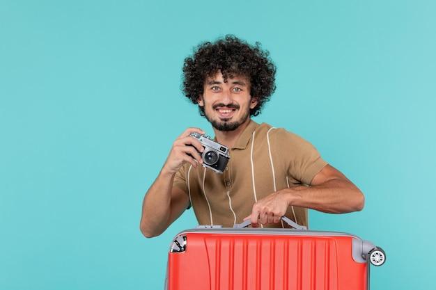 블루에 카메라와 함께 사진을 찍고 큰 가방으로 휴가에 남자