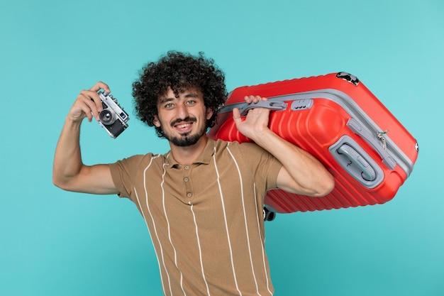 青のカメラで写真を撮る大きなスーツケースを持った休暇中の男