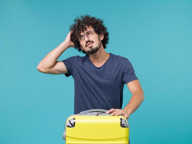 Человек в отпуске с большим чемоданом думает на синем