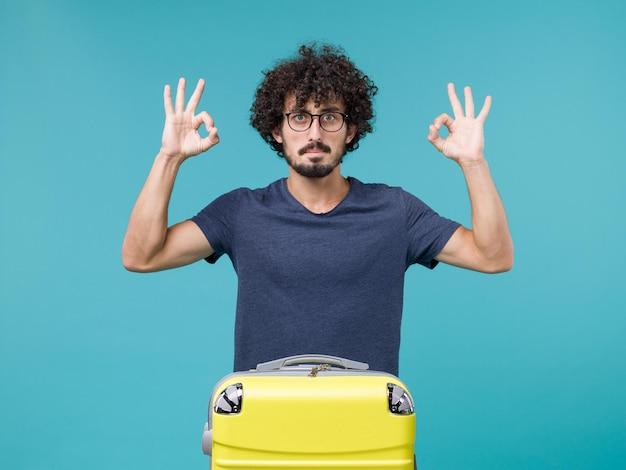 青に大きな黄色のスーツケースを持つ休暇中の男