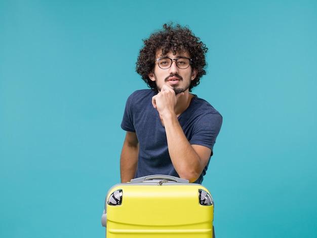 Человек в отпуске с большим желтым чемоданом на голубом
