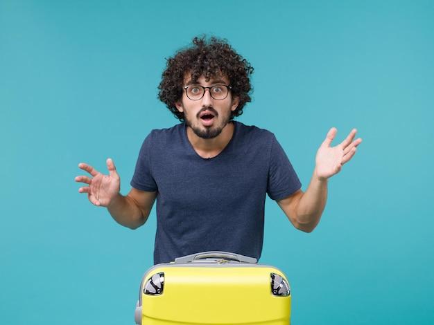 青に驚いた大きな黄色いスーツケースを持った休暇中の男性