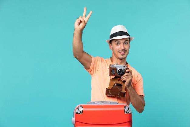 赤いスーツケースと水色のカメラで休暇中の男