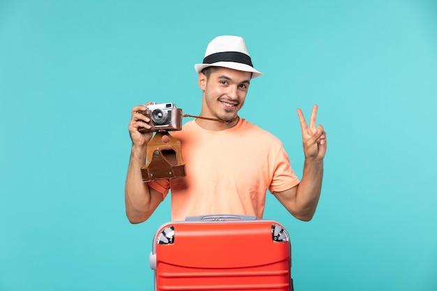 休暇中の男が赤いスーツケースを持ち、青のカメラで写真を撮る