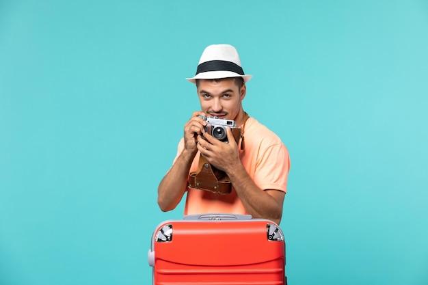 Человек в отпуске со своим красным чемоданом фотографирует с камерой на синем