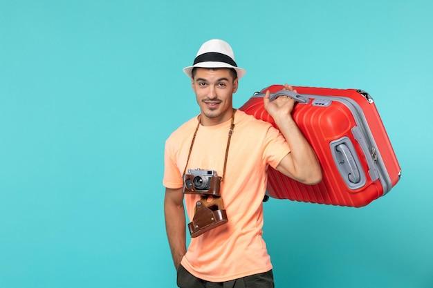Человек в отпуске с красным чемоданом и фотоаппаратом на синем