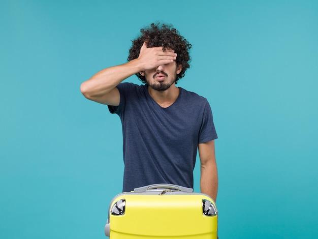 青に目を閉じて黄色いスーツケースを持った休暇中の男