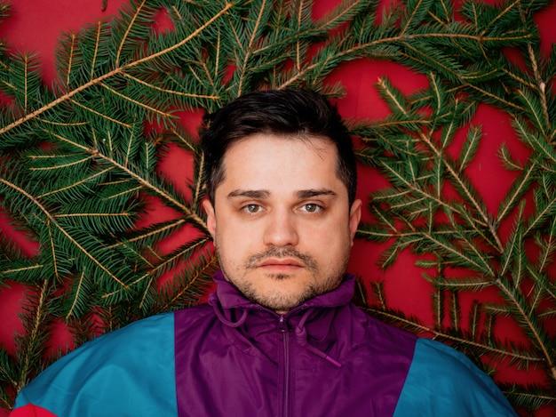빈티지 운동복을 입은 남자와 빨간색 배경에 전나무 가지가 누워 있는 남자