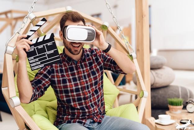 Человек в очках виртуальной реальности держит фильм клаппер.