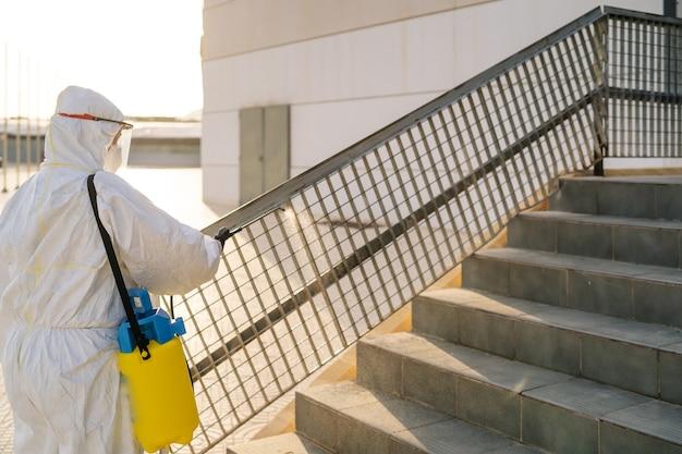ウイルス防護服を着た男性と、コロナウイルスの建物を噴霧器で消毒するマスク。感染予防とエピデミックの制御。世界的大流行。