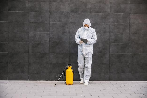 ウイルス防護服を着た男とマスクを探してタブレットで入力し、スプレーでcovid-19の建物を消毒します。感染の予防と流行の抑制。世界パンデミック。