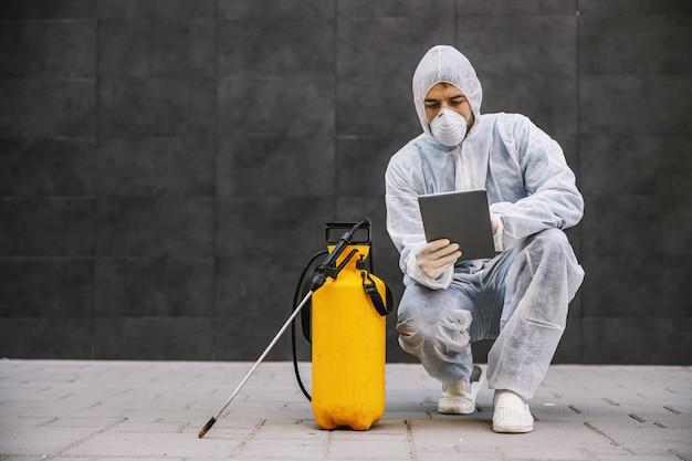 바이러스 보호 복을 입은 남자와 마스크를보고 태블릿에 타이핑하고 분무기로 코로나 19의 건물을 소독합니다. 감염 예방 및 전염병 통제. 세계 대유행.
