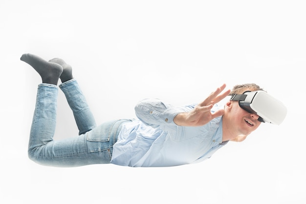 Vrメガネをかけた男が宙を舞う。白い背景で隔離。仮想ゲームの概念。