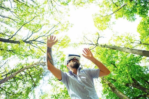 架空の現実を探索しながら空中でジェスチャーをするワイヤレスゴーグルのデジタルタッチスクリーンヒップスターを使用してvrメガネの男