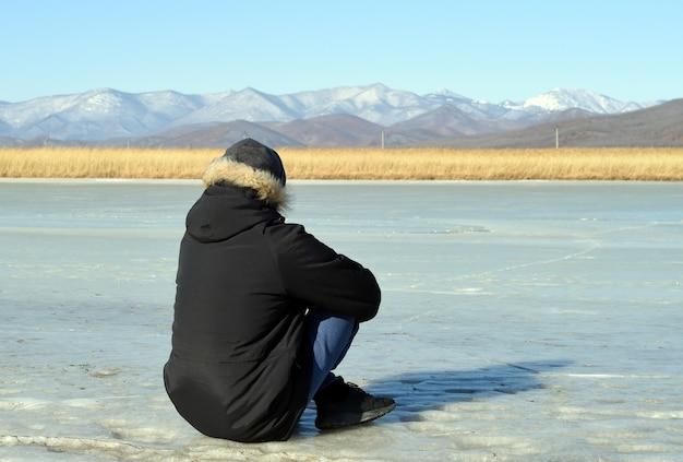 얼음에 앉아서 눈 덮인 산을 바라 보는 따뜻한 옷을 입은 남자