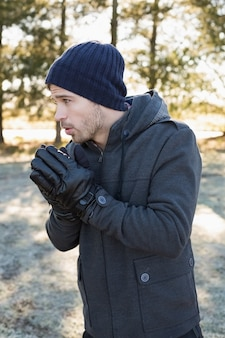 Человек в теплой одежде дрожит, гуляя в лесу