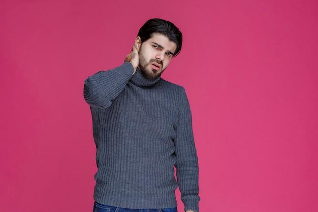 暖かいセーターを着た男性は、風邪を引いて病気になったようです。
