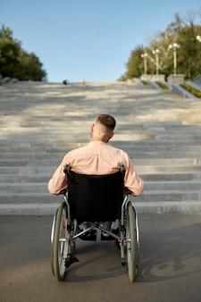 階段で車椅子の男、背面図