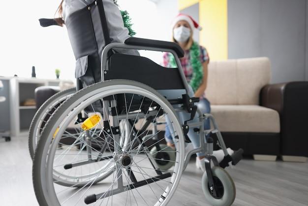 산타 클로스 모자에있는 여자 앞에서 휠체어에 남자