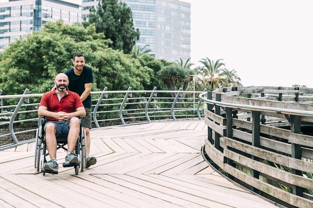 車いすの男が公園で友達と散歩