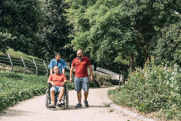 그의 관리인과 친구와 휠체어에 남자