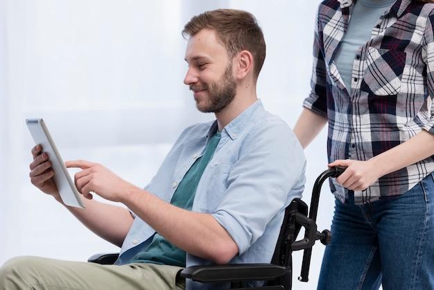 Человек в инвалидной коляске с планшета