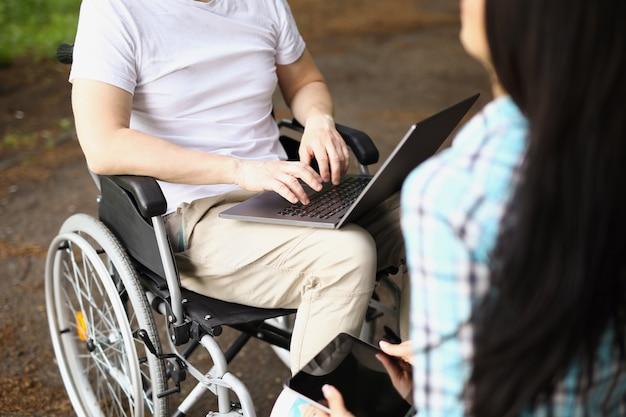 Мужчина в инвалидной коляске работает на ноутбуке на улице рядом с женщиной, сидит и держит планшет