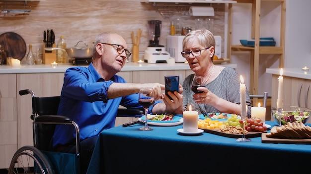 Человек в коляске с помощью смартфона сидит за столом на кухне во время романтического ужина. обездвиженный парализованный пожилой муж-инвалид ругается по телефону, наслаждаясь праздничным мужчиной.