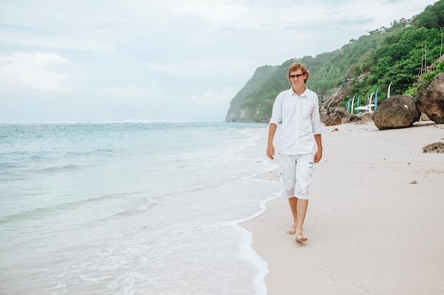 白いビーチを歩いている白い服を着た男