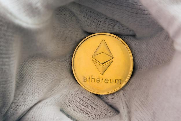 Человек в белых гвоздиках держит монету ethereum между ладонями.