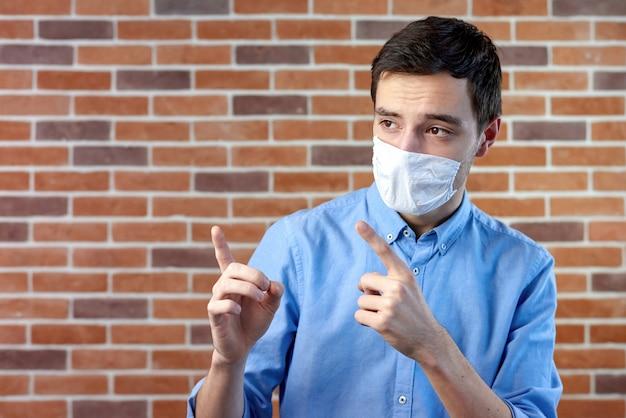 手で指している白い医療マスクの男
