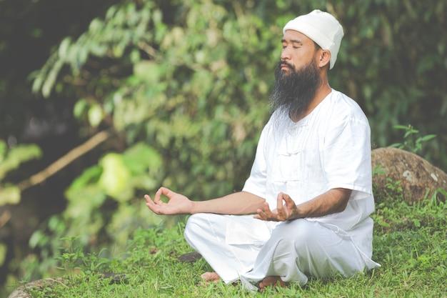 自然の中で瞑想する白い服を着た男