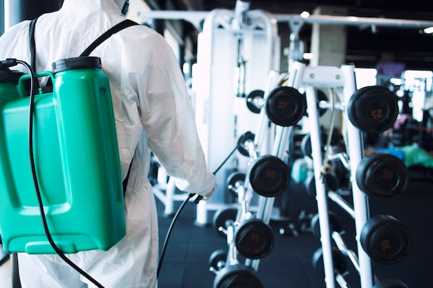 흰색 보호 복을 입은 남자는 전염성이 높은 코로나 바이러스의 확산을 막기 위해 소독 및 피트니스 장비 및 체중계를 착용하고 있습니다.