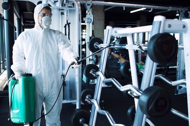 Мужчина в белом защитном костюме дезинфицирует оборудование и веса для фитнеса, чтобы остановить распространение очень заразного вируса короны