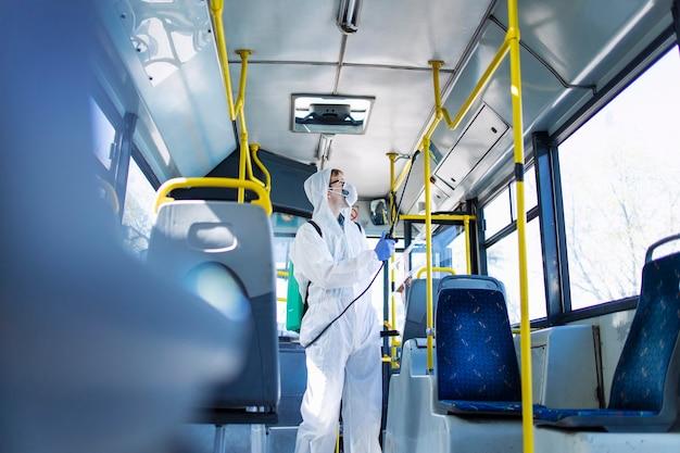 흰색 보호 복을 입은 남자가 핸들 바와 버스 내부를 소독하고 소독하여 전염성이 높은 코로나 바이러스의 확산을 막습니다.