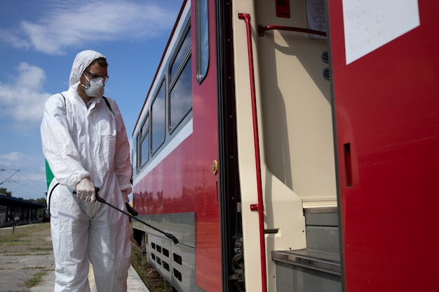 伝染性の高いコロナウイルスの拡散を防ぐために、地下鉄の電車の外壁を消毒および消毒する白い防護服を着た男